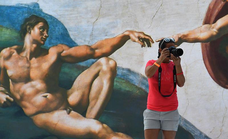 Eine Frau mit Kamera steht vor dem Gemälde Michelangelos, das die Erschaffung Adams zeigt