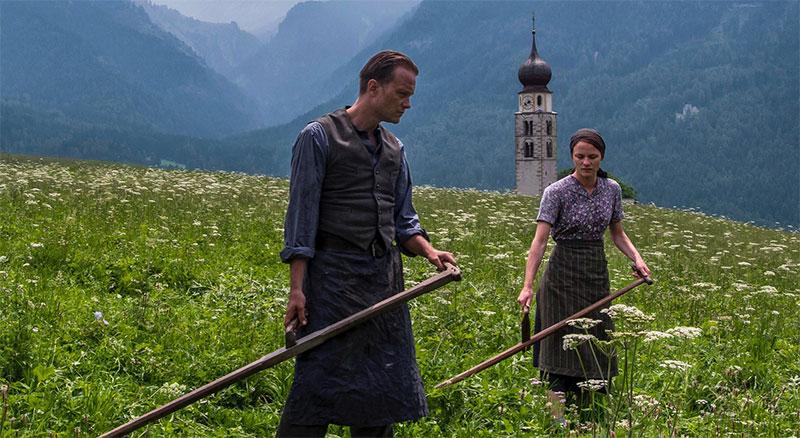 Radegund: Zwei Menschen mähen eine Wiese in den Bergen