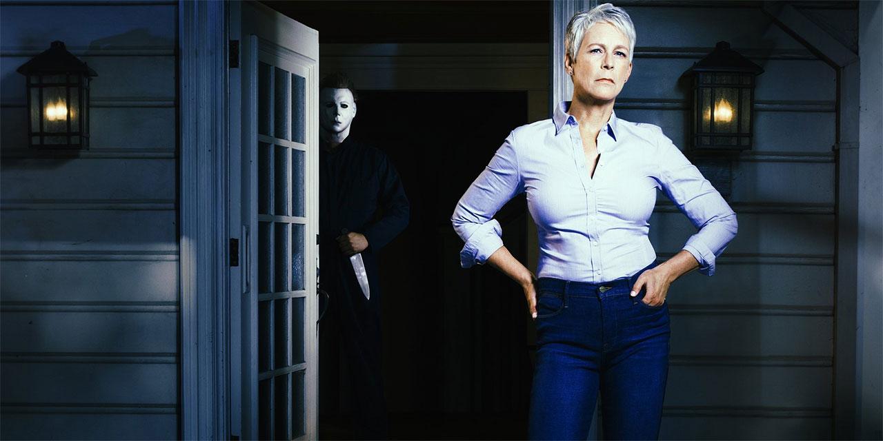 Halloween: Frau steht auf Veranda, hinter ihr im Haus eine maskierte Person mit Messer