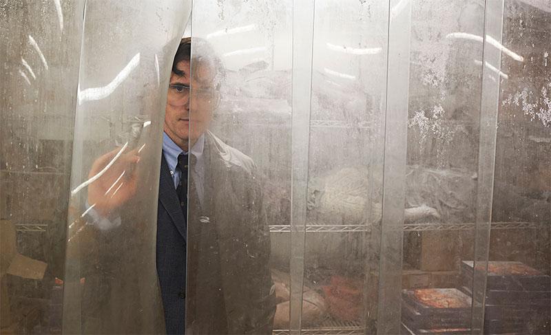Mann blickt durch Kunststoff-Vorhang eines Kühlraums, dahinter liegen Leichen