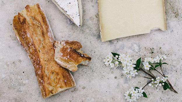 ein Stück Baguette Brot auf einem Tisch, außerdem sind Käse und Blumen zu sehen