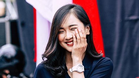 Portrait einer lachenden Frau mit asiatischen Zügen. Sie hat eine Hand an ihrer Wange.