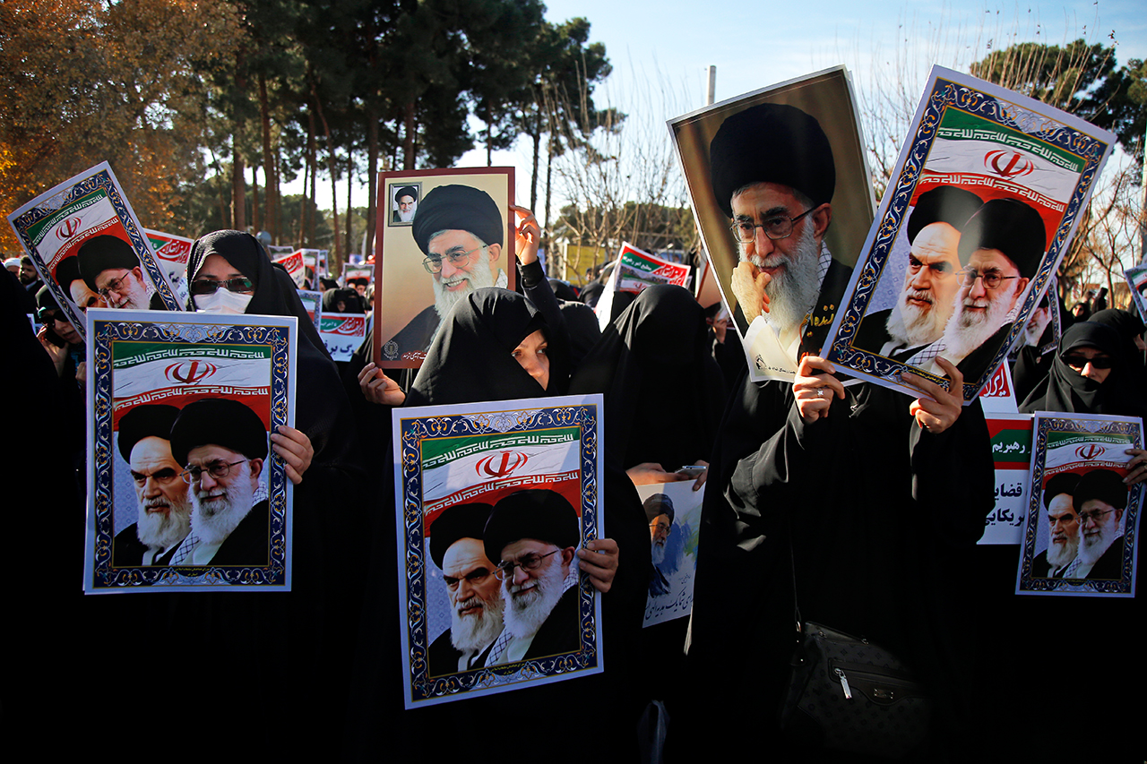 Pro-government demonstrators hold posters of Iran's supreme leader, Ayatollah Ali Khamenei (L) and Iran's founder of Islamic Republic, Ayatollah Ruhollah Khomein
