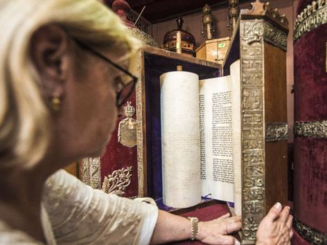 Eine Frau zeigt eine Torah-Rolle