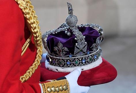 Imperial State Crown / mit Juwelen besetzte britische Krone wird auf einem roten Polster getragen