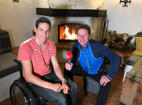 Lukas Müller im Rollstuhl und Ö3-Reporter Michi Kasper kockend vor einem Kamin