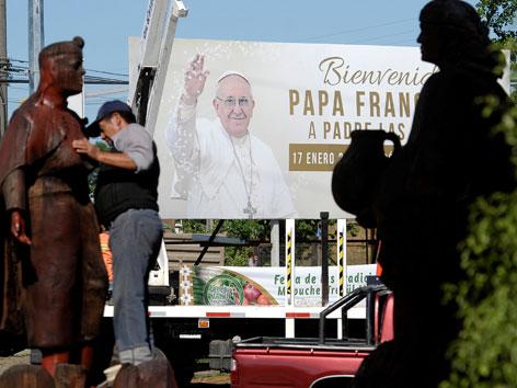 Ein Mann plaziert eine indigene Statue nahe eines Plakats mit Papst Franziskus als Vorbereitung auf den Papstbesuch in Temuco, Chile