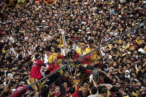"""Mehrere Millionen Menschen bei den """"Schwarzer Nazarener""""-Feiern in Manila (Philippinen), einige Gläubige tragen die Christusstatue"""