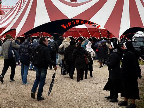 Nonnen und Obdachlose vor dem Eingang zu einem Zirkuszelt