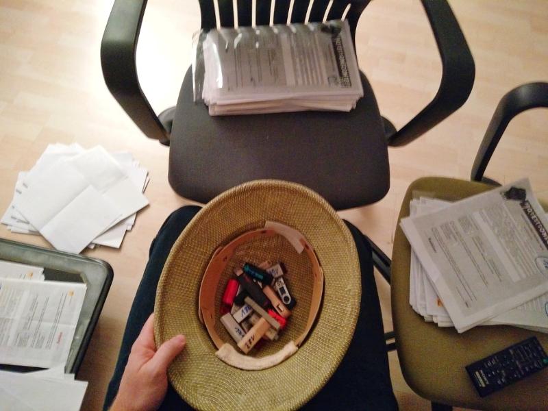 Ein Foto vom Auswahlverfahren: ein Safarihut mir USB-Sticks und mehrere Papierstapel verteilt auf einige Sessel.