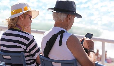 Ein älterer Mann tippt auf sein Smartphone, eine Frau sieht im zu