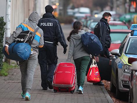 Abgeschobene Familie mit Koffern auf einem Gehsteig, in Begleitung von zwei Poizisten
