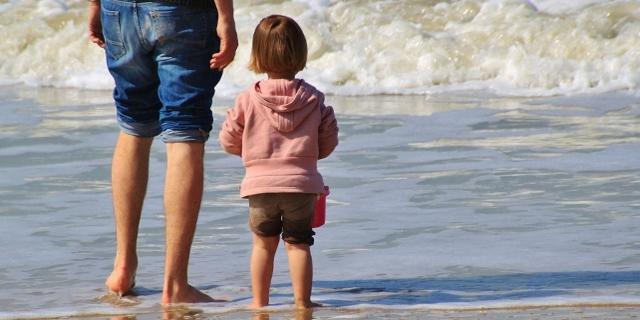 Ein Kind und ein Erwachsener schauen aufs Meer.