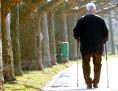 Ein Senior spaziert mit Nordic-Walking-Stöcken