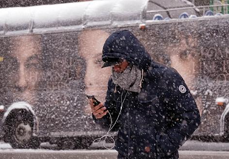 Ein Mann mit Kopfhörern blickt im dichten Schneetreiben auf sein Smartphone