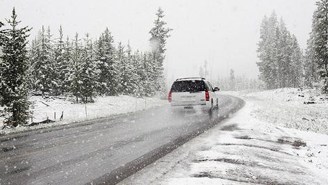 Auto fährt im Winter bei Schneefall, viel Schnee neben der Fahrbahn
