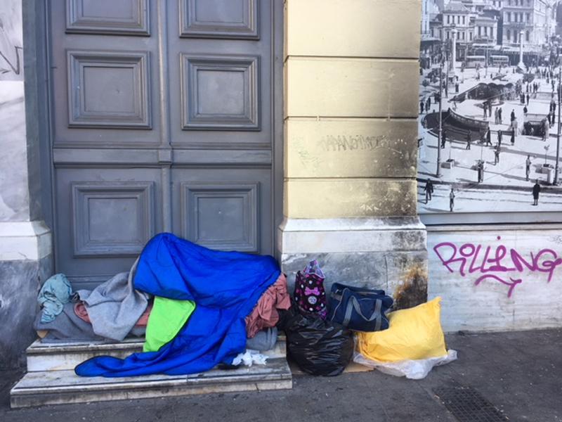 Obdachlosigkeit in Athen: Mensch schläft auf Haustorschwelle