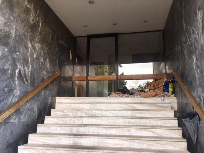 Obdachlosigkeit in Athen: Mensch schläft in Gebäudeeingang