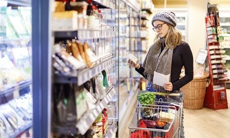 Frau liest Etikett mit Inhaltsstoffen im Supermarkt