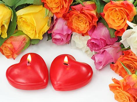 Zwei brennende Kerzen in Herzform neben Rosen