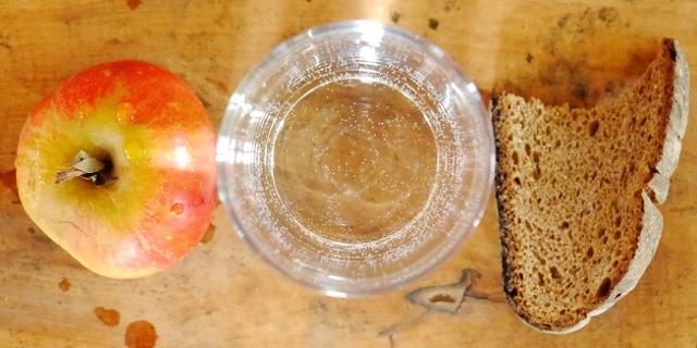 Apfel, leere Schale und ein Stück Brot