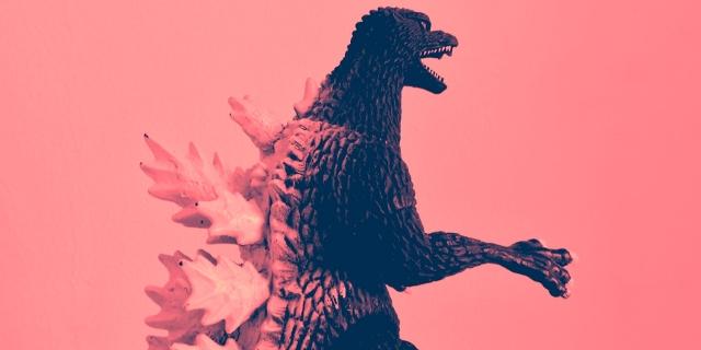 Godzilla Puppe vor rosa Hintergrund
