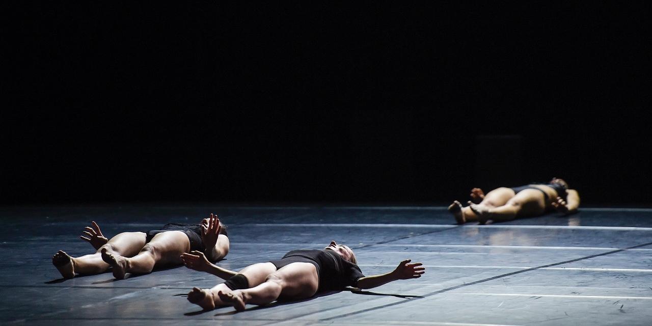 3 Schauspielerinnen oder Tänzerinnen liegen am Boden der Bühne