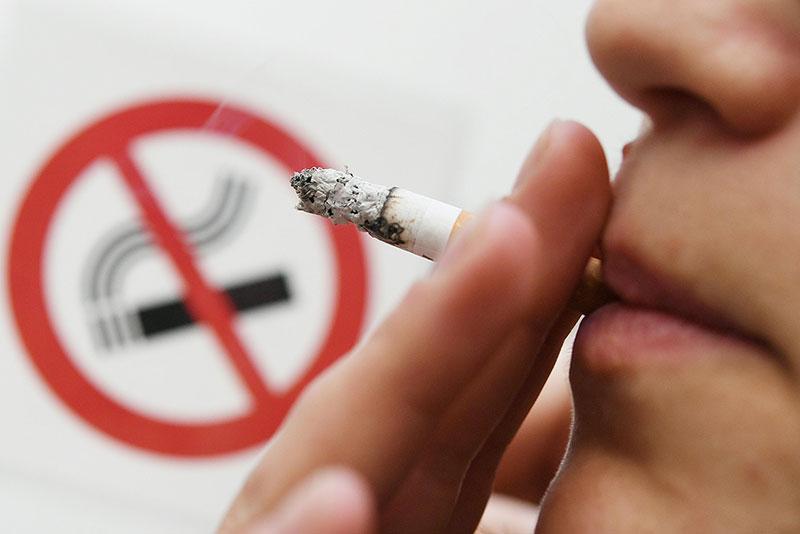 """Person raucht vor Schild """"Rauchverbot"""""""