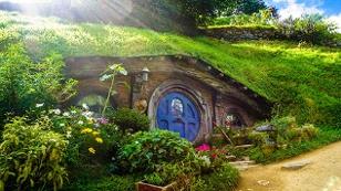 Hobbit Haus mit rundem blauen Tor im hügeligen Auenland
