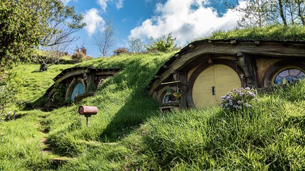 Zwei Hobbit Häuser mit runden Toren im hügeligen Auenland