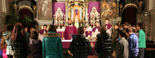 Altartotale während eines Gottesdienstes mit Pfarrer und jungen Menschen um den Altar