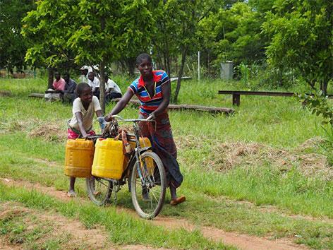 Frau und Kind transportieren Wasser mit einem MIVA-Fahrrad im Kongo
