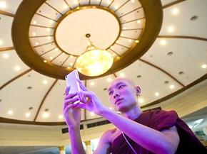 Ein buddhistischer Mönch macht ein Foto mit einem Smartphone