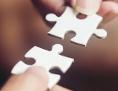 Zwei Puzzleteile werden von zwei Menschen ineinandergesteckt