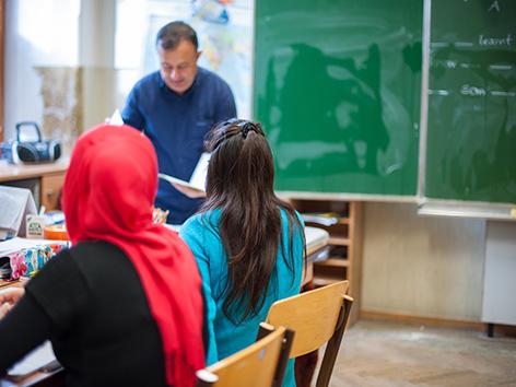 Zwei Mädchen von hinten in einer Klasse in einer Schule. Ein Mädchen mit Kopftuch.