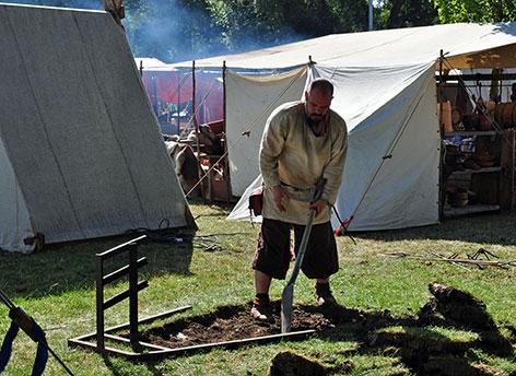 Mann mit Schaufel vor Zelten bei den Wikingertagen