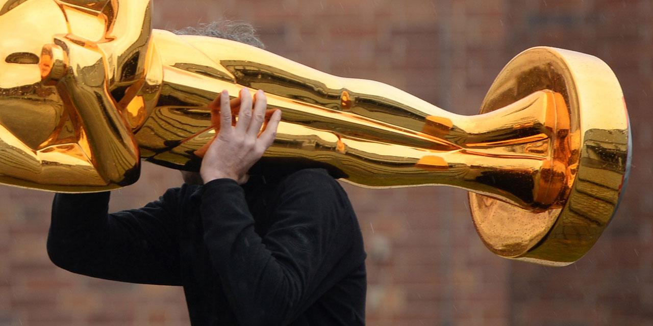 Mann trägt große Oscar-Statue auf der Schulter