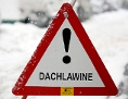 """Ein Warnschild mit der Aufschrift """"Dachlawine"""" im Schnee"""