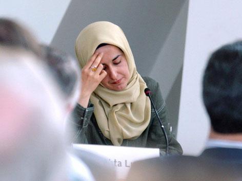 Eine Frau mit Kopftuch bei einem Rednerpult