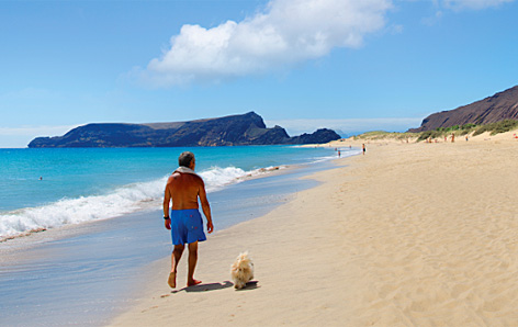 Ein Mann spaziert mit Hund den Strand von Madeira entlang