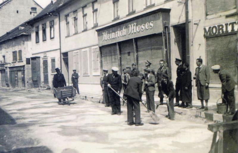 """Juden aus Mattersburg, Burgenland, müssen die Straßen säubern. SA-Männern bewachen sie, die Ortsbevölkerung sieht zu."""""""