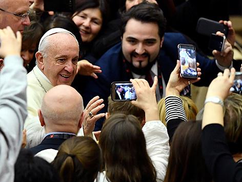 Papst Franziskus in einer Menge mit mehreren hochgehaltenen Smartphones