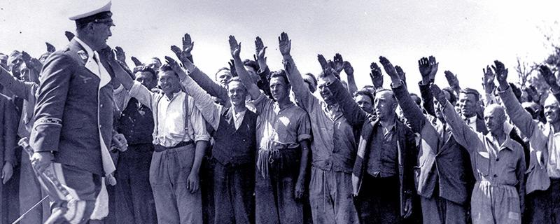 Mehrere Menschen heben glücklich die Hand zum Hitlergruß, während ein NS-Funktionär vor ihnen paradiert
