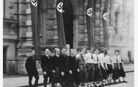 Studenten der Fachschaft Evangelische Theologie vor dem mit Hakenkreuzfahnen beflaggten Fakultätsgebäude Liebiggasse 5