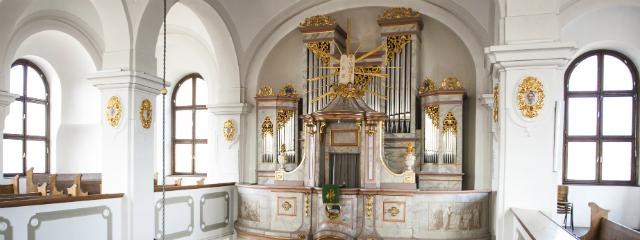 Orgel und weiße Gebotstafeln in goldenem Strahlenkranz zwischen hellen, großen Kirchenfenstern