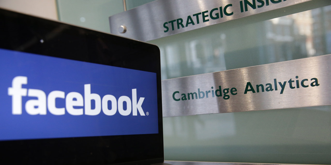 Facebook-Logo neben Cambridge-Analytica-Schild