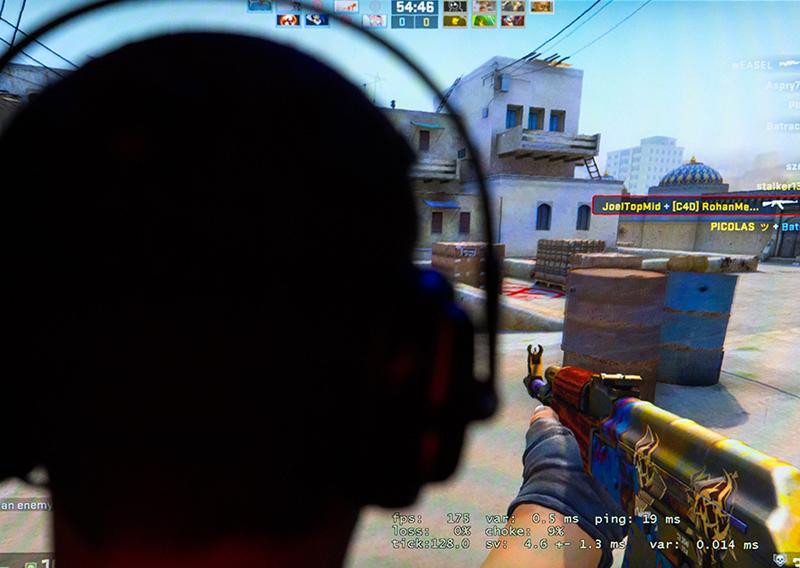 Ein Mann mit Kopfhörer spielt ein Shooter-Spiel.