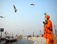 Ein indischer Sadhu beim Gebet an einem Hafen