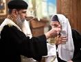 Ein koptischer Priester erteilt einer Frau die Kommunion in Road al-Farag, Kairo
