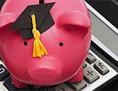 Sparschwein mit akademischem Hut auf einem Taschenrechner